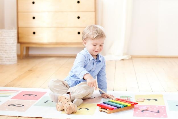 De jongen speelt in een kleuterschool op de xylofoon. jongen speelt met speelgoed muziekinstrument xylofoon in de kinderkamer. close-up van een kind dat op xylofoon speelt. het concept van kinderontwikkeling. Premium Foto