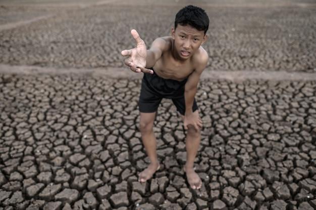 De jongen stond gebogen op zijn knieën en maakte een teken om regen, opwarming van de aarde en watercrisis te vragen. Gratis Foto