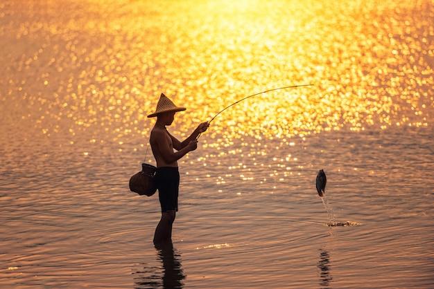 De jongen vist bij zonsondergang op het meer Premium Foto
