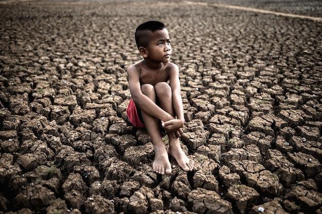 De jongen zit gebogen op zijn knieën en kijkt naar de lucht om regen op droge grond te vragen. Gratis Foto