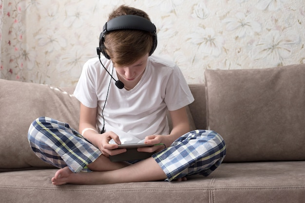 De jongen zit op de bank met een koptelefoon en speelt videogames op de telefoon Premium Foto