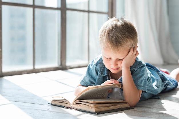 De jongensboek van de blondejongen dichtbij het venster in het zonlicht Gratis Foto