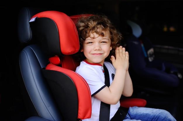 De jongenszitting van de baby in een rode autokinderzitje Premium Foto