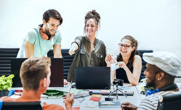 De jongerenwerknemers groeperen arbeiders met computer in startstudio Premium Foto