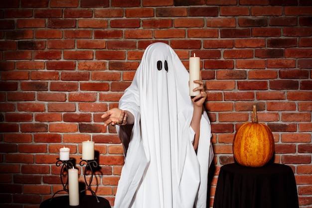 De kaars van de spookholding, die hand uitrekken aan. halloween feest. Gratis Foto
