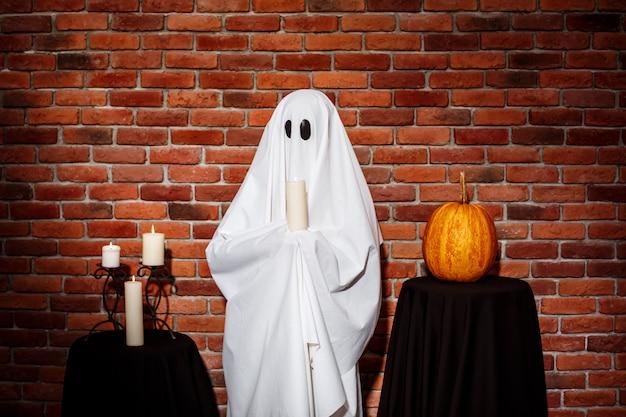 De kaars van de spookholding over bakstenen muur. halloween feest. Gratis Foto