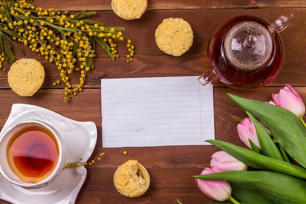 De kaart van de de daggroet van vrouwen met tulpen, mimosa, thee en cupcakes op bruine houten achtergrond. Premium Foto