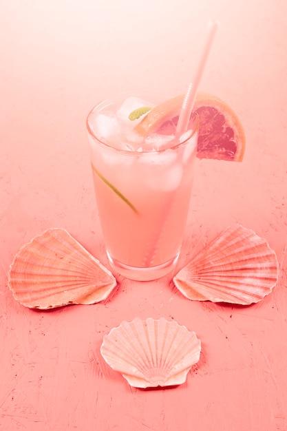 De kammosselzeeschelp dichtbij de koude grapefruitalcoholcocktail misted binnen glas met munt en grapefruits plak op koraal geweven achtergrond Gratis Foto