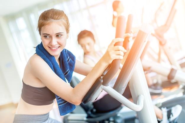 De kaukasische sportvrouw geniet van training met tredmolen in gymnastiekgeschiktheidscentrum met groep mensen Premium Foto