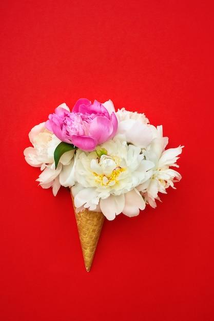 De kegel van het wafelroomijs met witte en roze pioenbloemen op rode achtergrond. Premium Foto