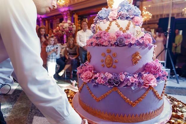 De kelner draagt luxueuze violette verfraaide huwelijkscake Gratis Foto