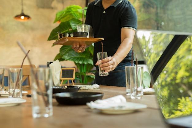De kelner haalt met de hand lege glazen en vuile vaat op dinerrestaurant op. Premium Foto