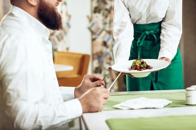 De kelner van het meisje dient zijn schotel in restaurant aan een man Premium Foto