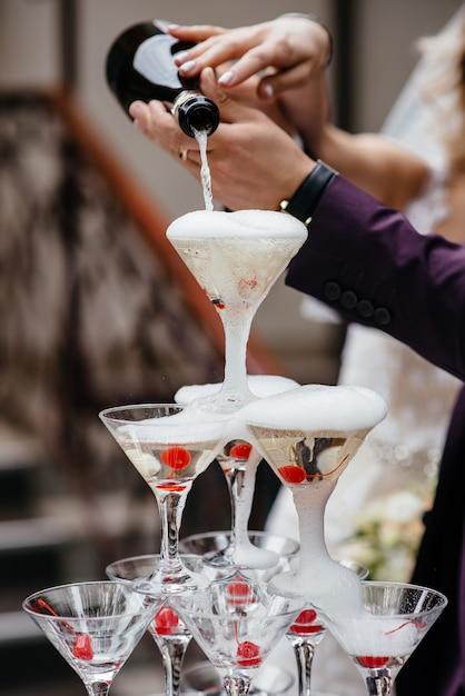 De kelner vulde de glazen piramide van de champagnefontein Premium Foto