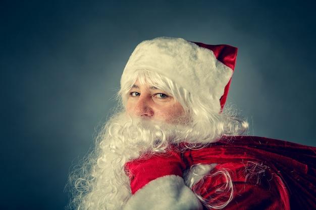 De kerstman draagt een tas met cadeautjes. kerst fantasie. Premium Foto