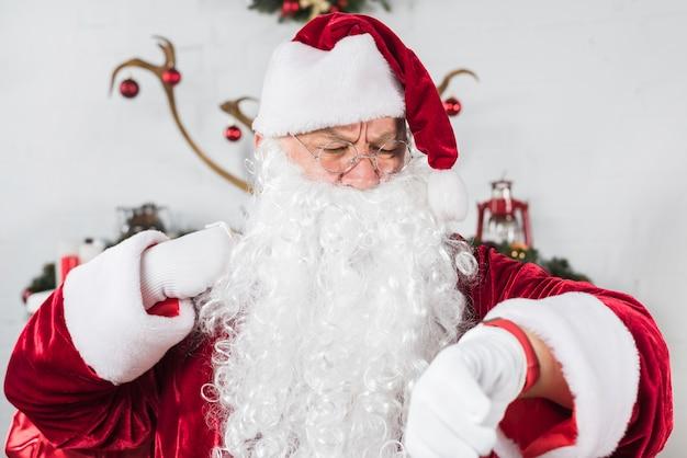 De kerstman in glazen die tijd controleren op polshorloge Gratis Foto
