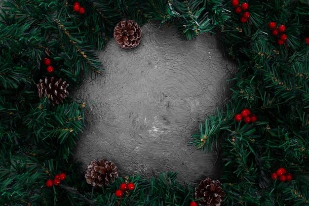 De kerstmispijnboom verlaat kader op een grunge grijze achtergrond Gratis Foto