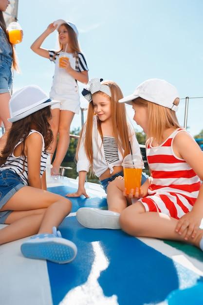De kinderen aan boord van een zeejacht drinken sinaasappelsap. de tiener of kindmeisjes tegen blauwe hemel openlucht. kleurrijke kleding. concepten voor kindermode, zonnige zomer, rivier en vakantie. Gratis Foto