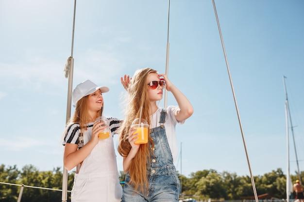 De kinderen aan boord van een zeejacht drinken sinaasappelsap Gratis Foto