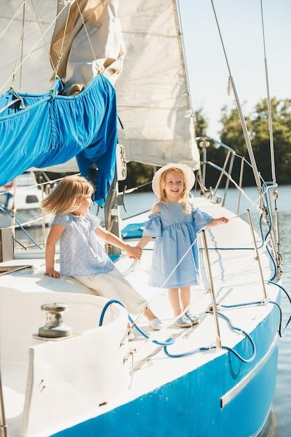 De kinderen aan boord van een zeiljacht. de tiener- of kindmeisjes buiten. kleurrijke kleding. concepten voor kindermode, zonnige zomer, rivier en vakantie. Gratis Foto