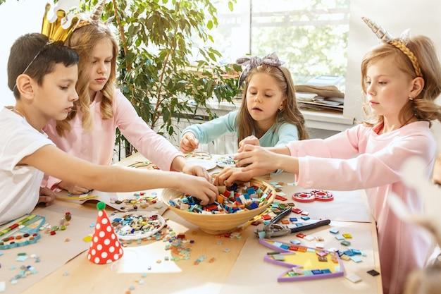 De kinderen en verjaardagsdecoratie. de jongens en meisjes aan tafel met eten, gebak, drankjes en feestgadgets. Gratis Foto