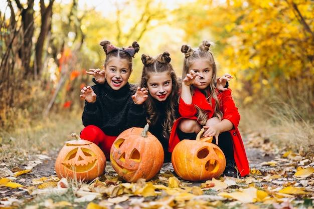 De kinderenmeisjes kleedden zich in openlucht in halloween-kostuums met pompoenen Gratis Foto
