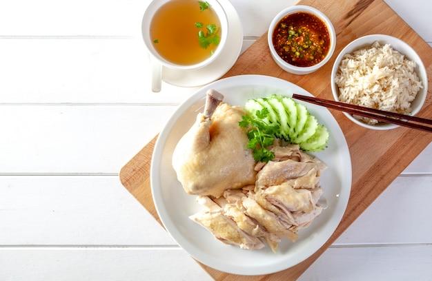 De kippenrijst van hainanese, gestoomde kip met rijst, khao mun kai op houten achtergrond Premium Foto