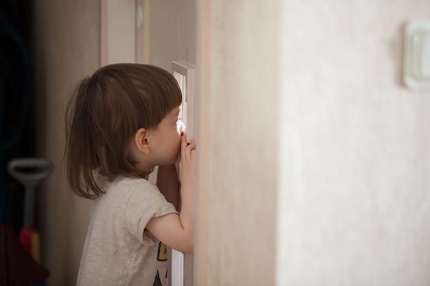 De kleine jongen kijkt in het raam van de deur. Premium Foto