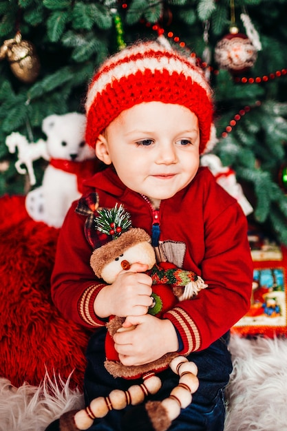 De kleine jongen koestert zijn klein stuk speelgoed vóór een kerstboom Premium Foto