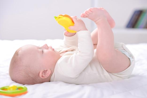 De kleine jongen speelt speelgoed op de wieg. Premium Foto
