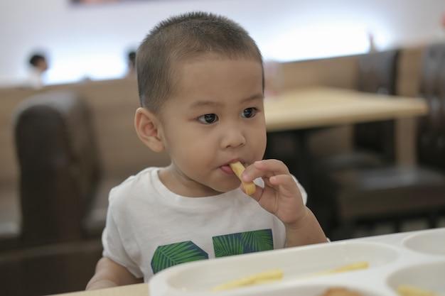 De kleine jongen was gelukkig aan het lunchen. gelukkig een familietijd. Premium Foto
