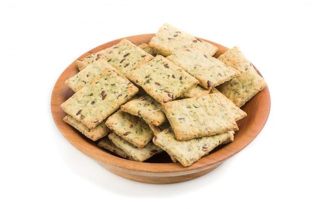 De kleine koekjes van broodspaanders met zaden in een houten die kom op wit wordt geïsoleerd. zijaanzicht Premium Foto