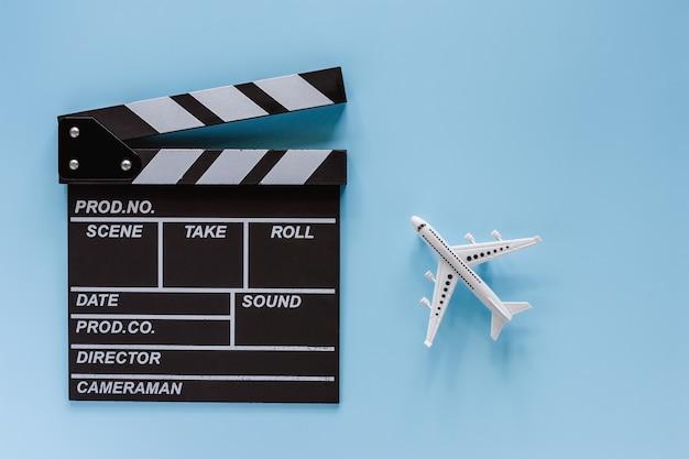 De kleppenraad van de film met wit vliegtuigmodel op blauwe achtergrond Premium Foto