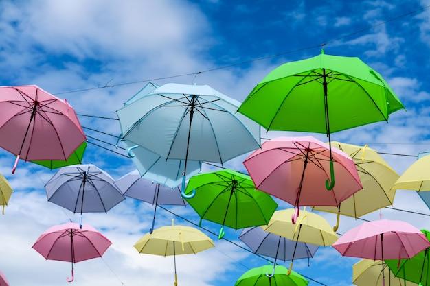 De kleurrijke buitensporige paraplulijn verfraait het openlucht bewegen door wind op blauwe hemel witte wolk Premium Foto