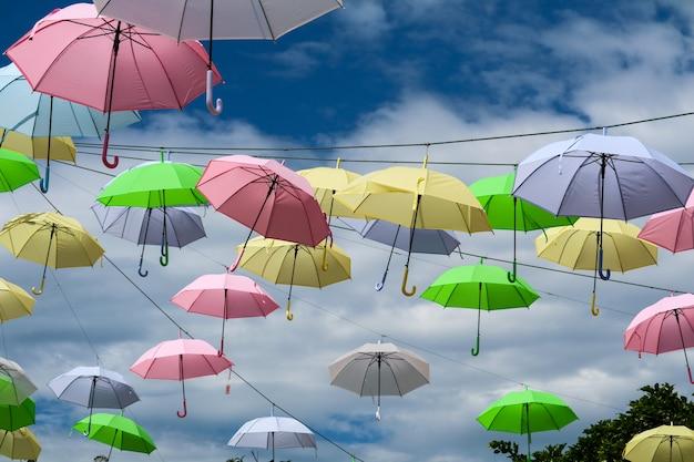De kleurrijke draad die van de paraplulijn zich door wind op blauwe hemel bewegen Premium Foto