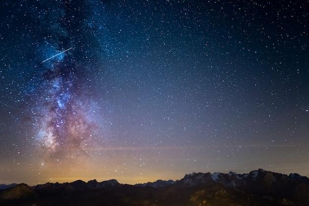 De kleurrijke gloeiende melkweg en de sterrenhemel boven de franse alpen en het majestueuze massif des ecrins. Premium Foto