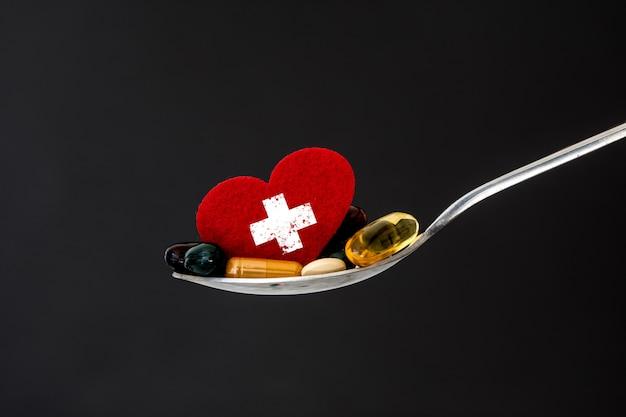 De kleurrijke medische aanvulling en drugs pillen met rood hart in lepel Premium Foto