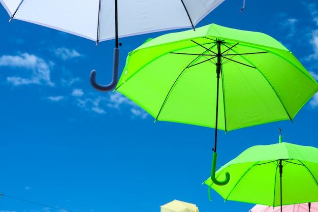De kleurrijke paraplulijn verfraait het openlucht bewegen door wind op blauwe hemel witte wolk Premium Foto