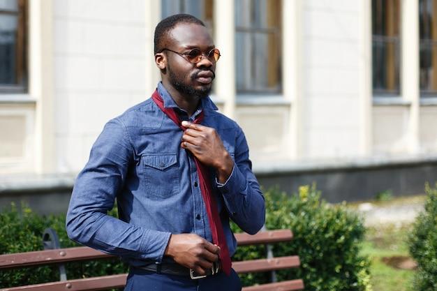 De knappe afrikaanse amerikaanse mens bevestigt zijn rode band op blauw overhemd die zich buiten bevinden Gratis Foto