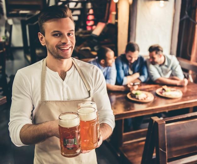 De knappe barman in schort houdt bier. Premium Foto