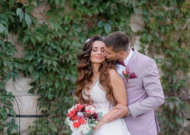 De knappe bruidegom kust in openlucht mooie bruid gekleed in modieuze huwelijkskledij Gratis Foto