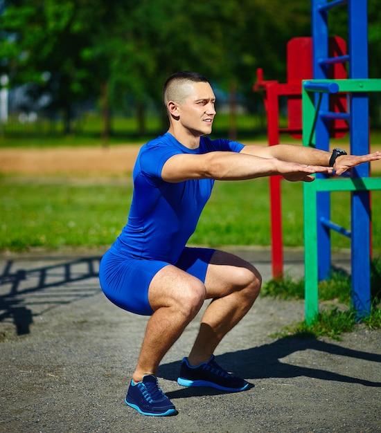 De knappe gezonde mannelijke mens die van de srtongatleet bij het stadspark uitoefenen - geschiktheidsconcepten op een mooie de zomerdag dichtbij rekstok Gratis Foto