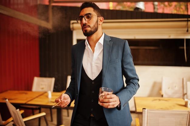 De knappe goed geklede arabische sigaar van de mensenrook met glas whisky bij balkon van bar. Premium Foto