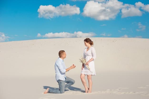 De knappe kerel doet het meisje een huwelijksaanzoek, buigt zijn knie, staand op het zand in de woestijn. Premium Foto