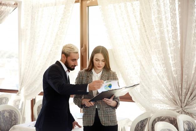 De knappe man en een donkerbruine vrouw bekijken het diagram, zijnd in de lichte ruimte Gratis Foto