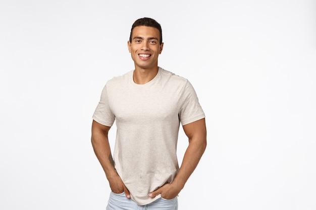 De knappe mannelijke atleet in toevallige t-shirt, houdt handen en zakken in die met gelukkig glimlachen Premium Foto