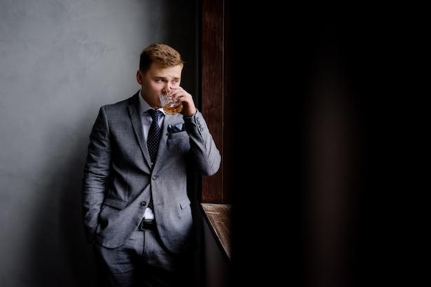 De knappe mens in formele kleding drinkt alcoholdrank en kijkt door het venster Gratis Foto