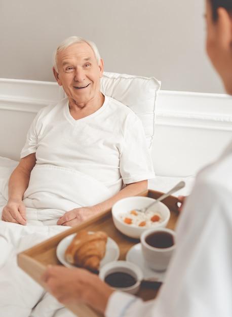 De knappe oude patiënt krijgt zijn maaltijd van verpleegster. Premium Foto