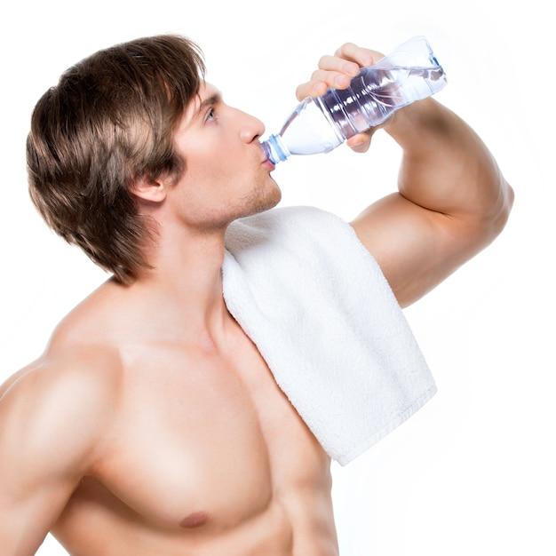 De knappe spier shirtless sportman drinkt water - dat op witte muur wordt geïsoleerd. Gratis Foto