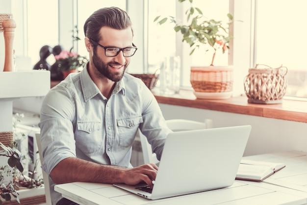 De knappe zakenman in oogglazen gebruikt laptop. Premium Foto